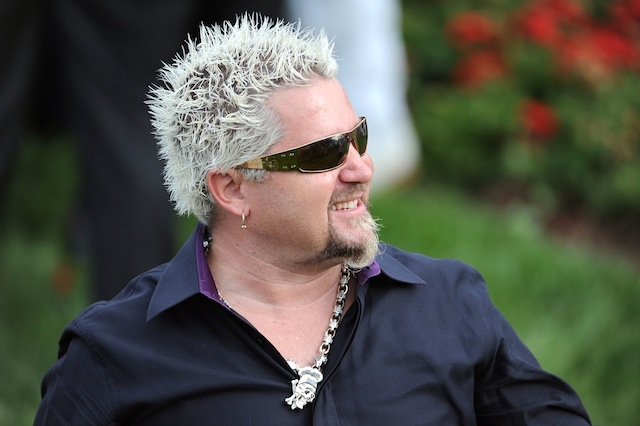 Guy Fieri plays with his food
